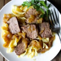 Beer braised beef and onions over egg noodles with fork