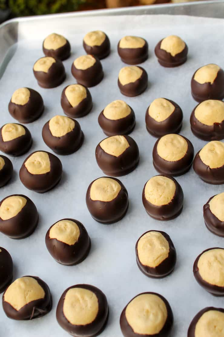 Buckeyes on lined sheet pan after dipping in chocolate