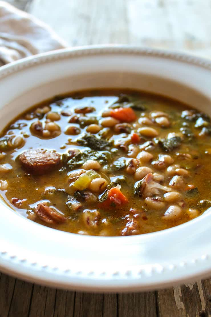 Black eyed pea soup and collard greens in serving bowl.