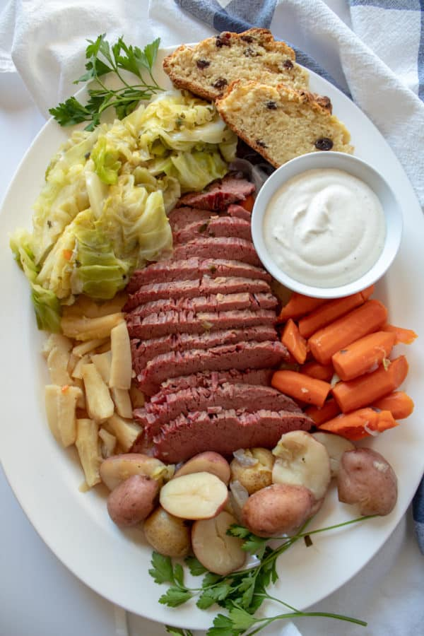Instant Pot Corned Beef and Cabbage, arranged on platter with horsereadish sauce and Irish soda bread.