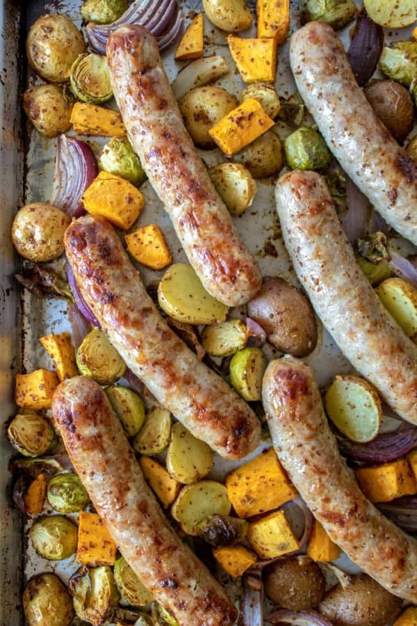 Sausages and caramelized vegetables on sheet pan.