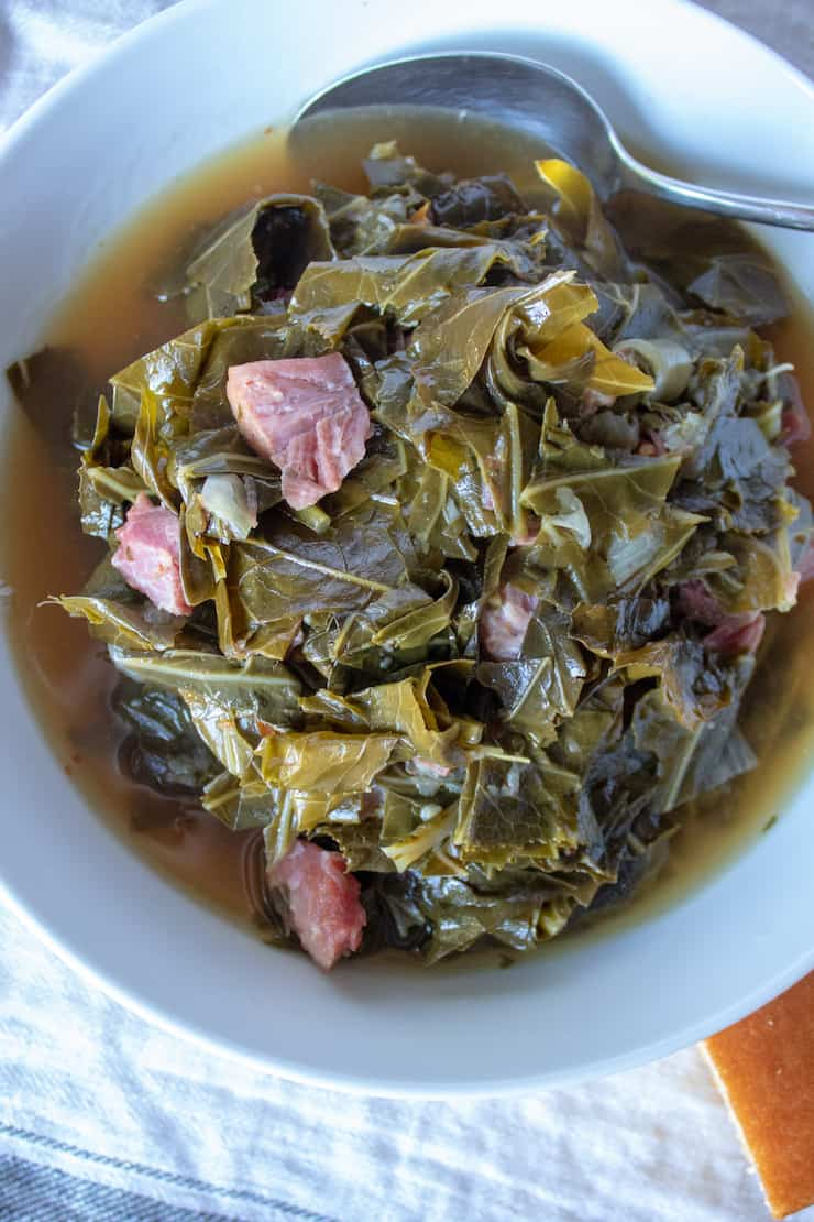 Instant Pot Collard Greens, in serving bowl with spoon and cornbread on side.