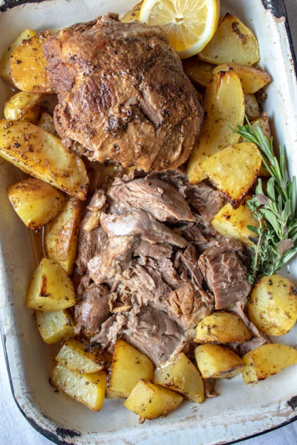 Greek Instant Pot Leg of Lamb, sliced and arranged in pan, surrounded with Greek potatoes.