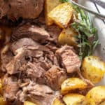 Greek Instant Pot Leg of Lamb, close up in pan with roasted potatoes.
