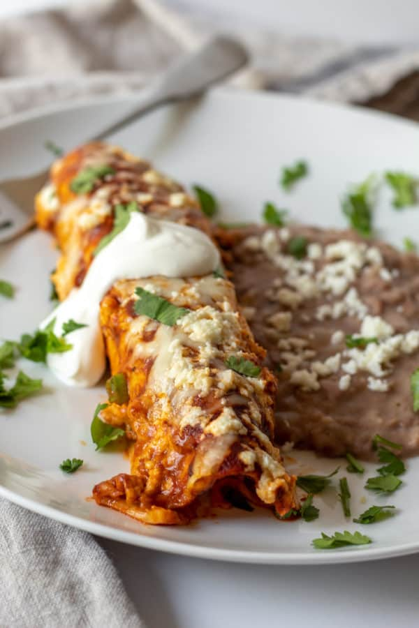 Enchilada on white plate with refried beans.