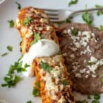 Ground turkey enchilada on plate with refried beans.