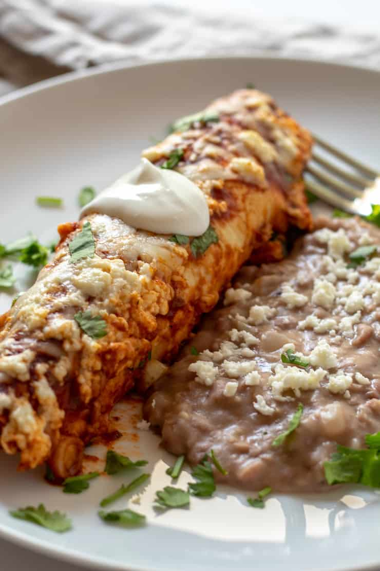 Turkey enchilada on plate with refried beans.