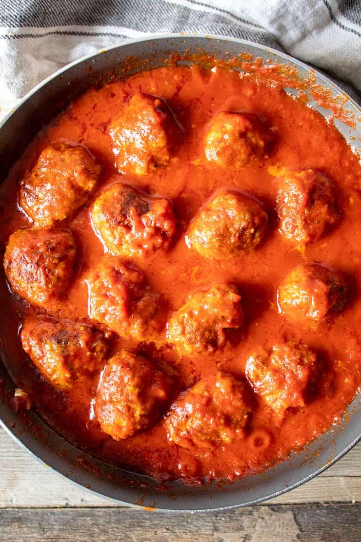 Meatballs simmering in sauce in skillet.