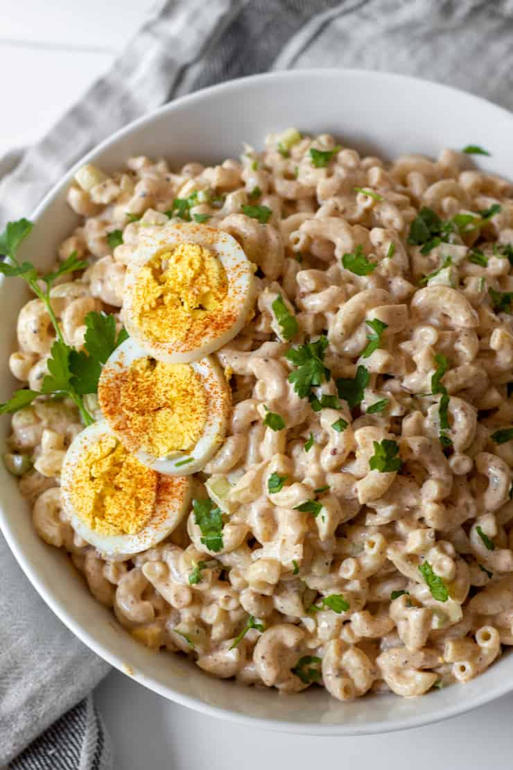 Overhead of Cajun macaroni salad in serving bowl garnished with hardboiled egg.