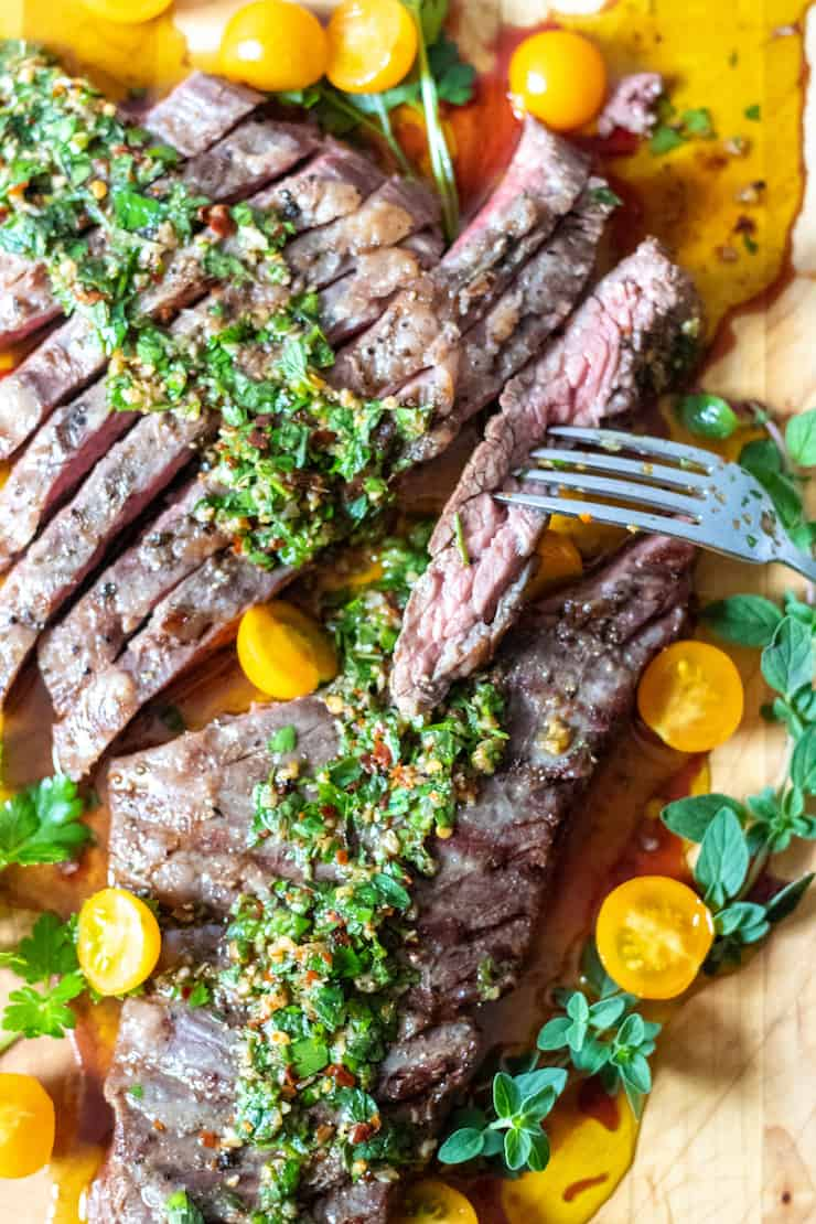Overhead of steak with chimichurri and tomatoes with close up on fork.