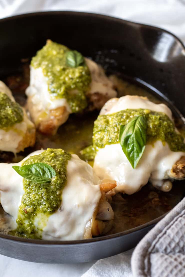 Close up of pesto mozzarella chicken in skillet.