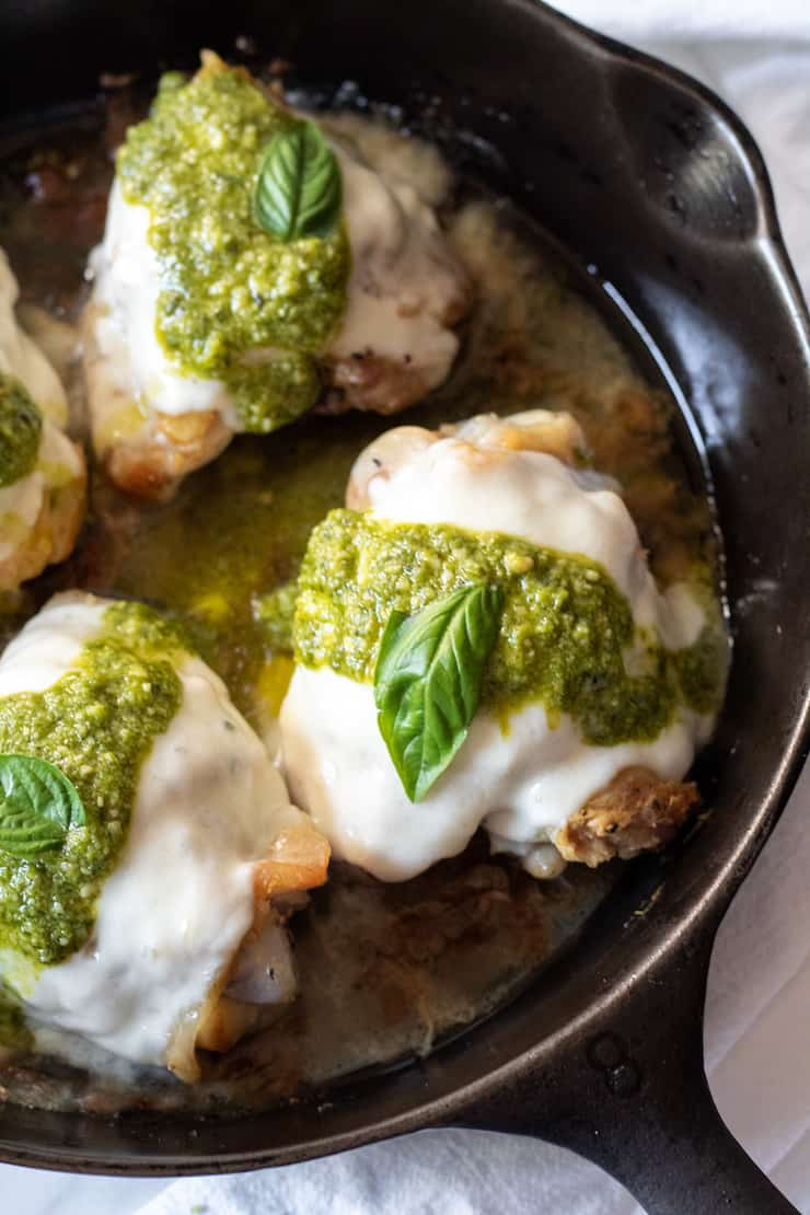 Close up of pesto mozzarella chicken in pan.
