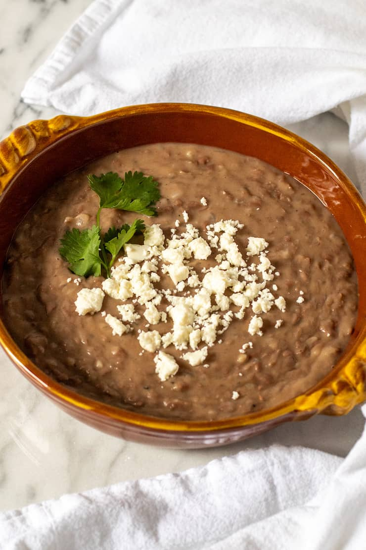 Refried beans in serving dish with queso fresco.