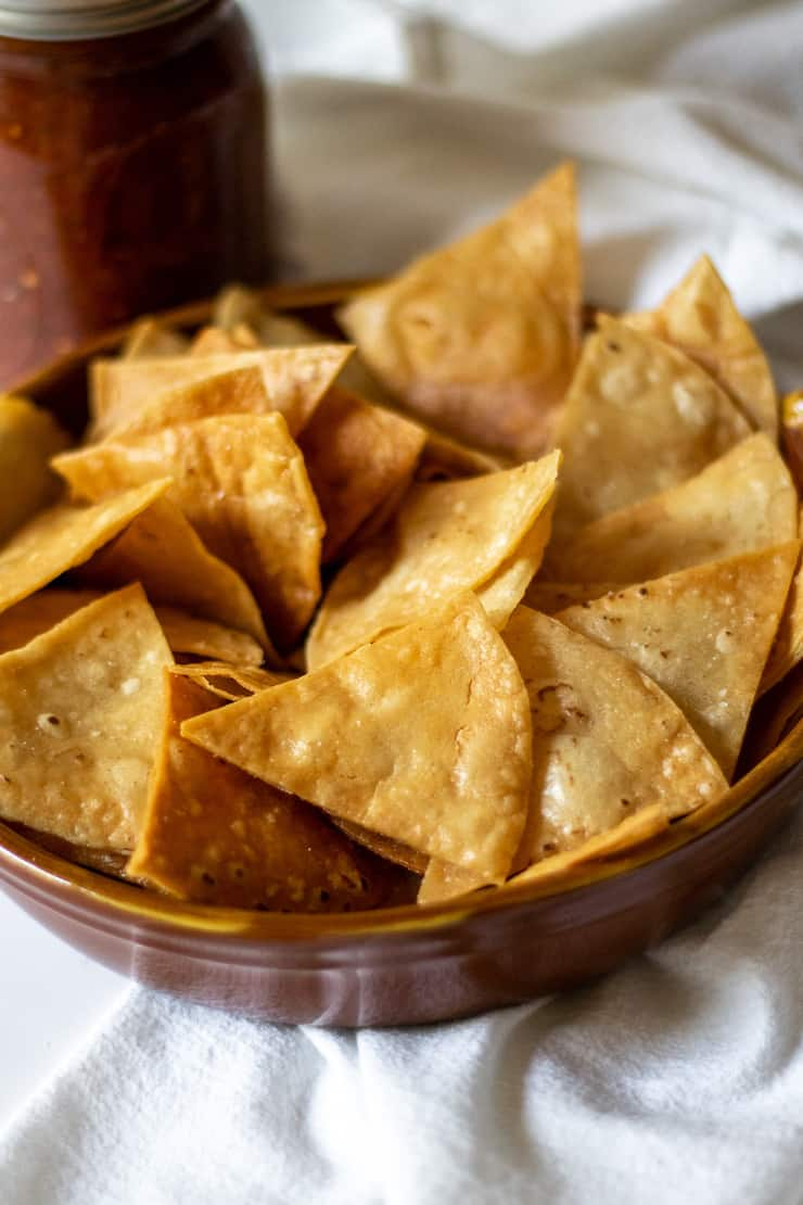 Bowl of chips with salsa in background.