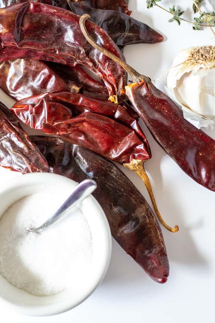 Ingredients close up of guajillo chiles, salt, garlic and oregano.