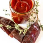 Enchilada sauce in jar surrounded by chiles and oregano.