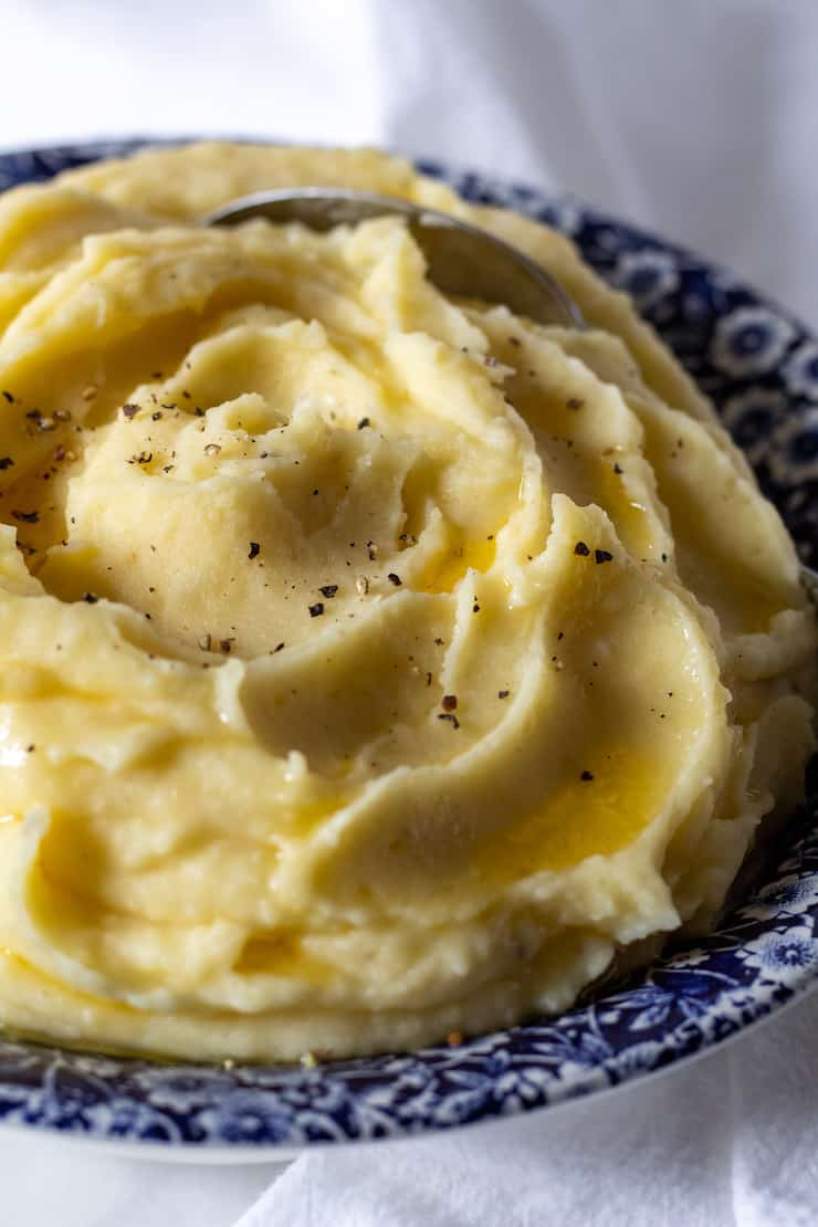 Finished mashed potatoes in bowl with drizzled melted butter and pepper.