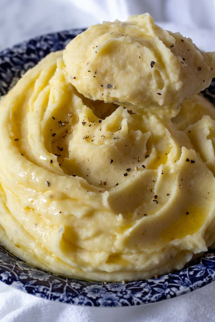 Garlic buttermilk mashed potatoes in serving bowl with close up of spoonful.