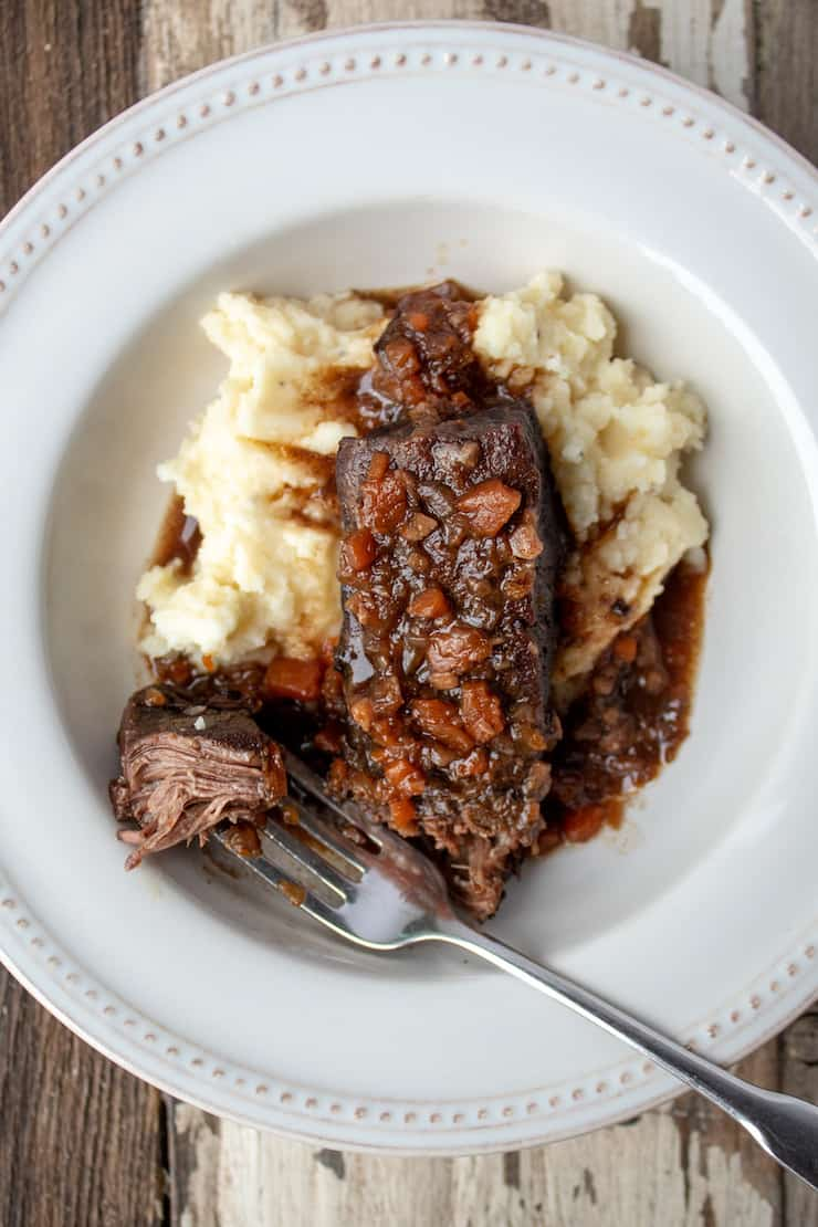 Short ribs plated with mashed potatoes and sauce, showing forkful of beef.