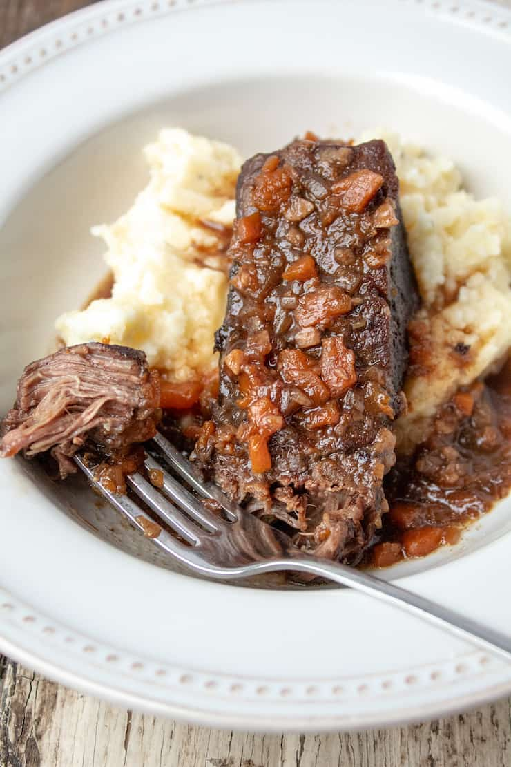 Instant Pot braised short ribs in bowl with mashed potatoes, forkful of meat on side.