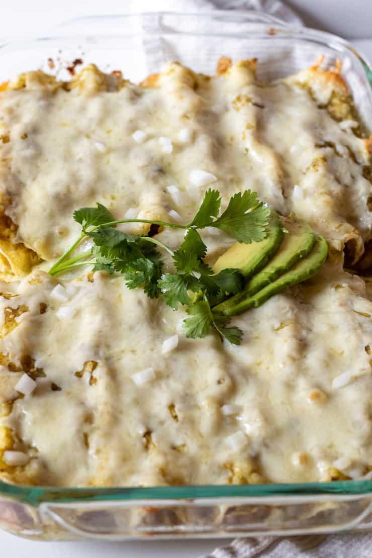 Pan of baked enchiladas verdes with garnish.