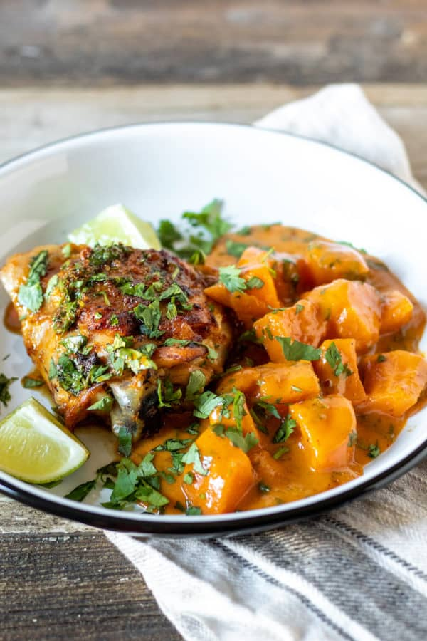 Curried sweet potatoes and skillet chicken on serving plate with lime wedges.