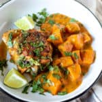 Sweet Potato curry with chicken thigh on plate garnished with lime and cilantro.