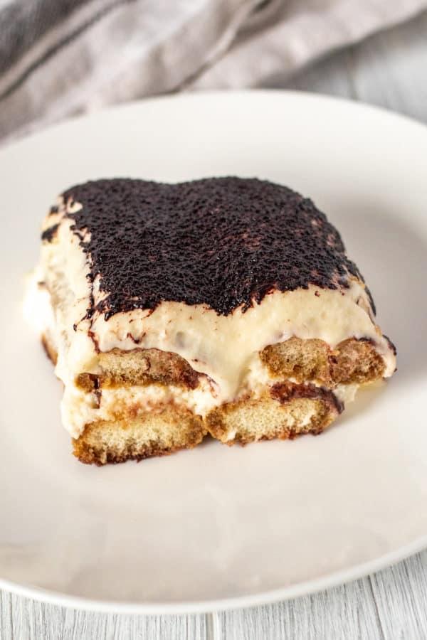 Tiramisu dessert slice on white plate.