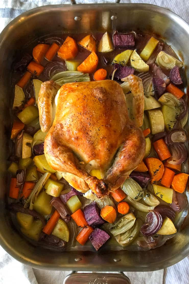 Roasted chicken over vegetables in roasting pan.