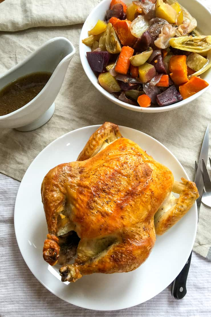 Roast chicken on tables with vegetables and pan juices.