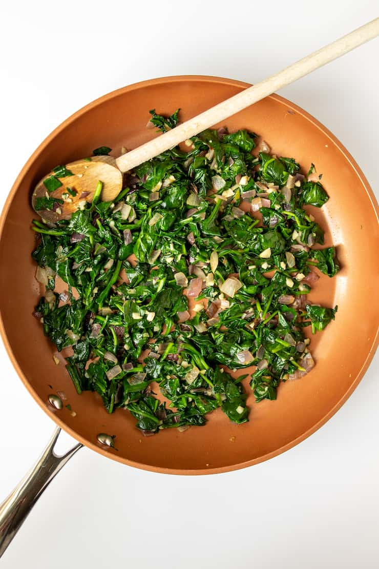Sautéed spinach with garlic and onion in skillet.