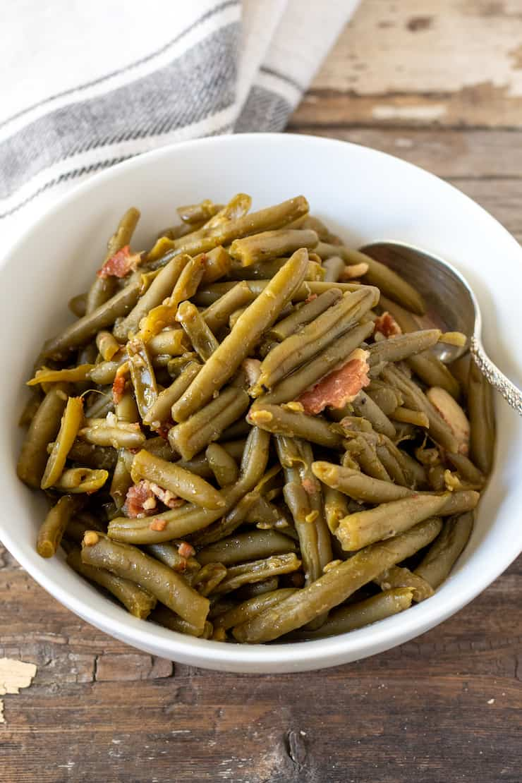 Southern green beans in serving bowl with spoon.