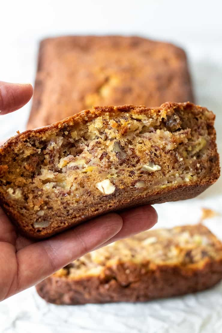 Hand holding slice of quick bread.