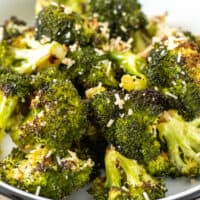 Oven roasted broccoli in serving dish with parmesan.