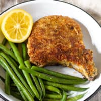 Breaded pork chop plated with green beans and lemon.