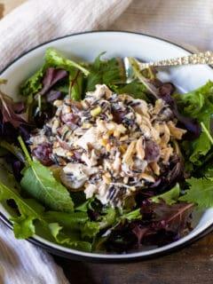 Mound of wild rice chicken salad over greens.