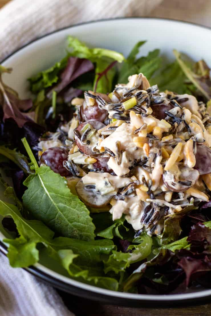 Wild rice chicken salad plated over mixed greens.