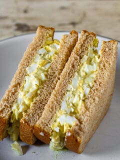 Egg salad sandwich cut in half on plate.