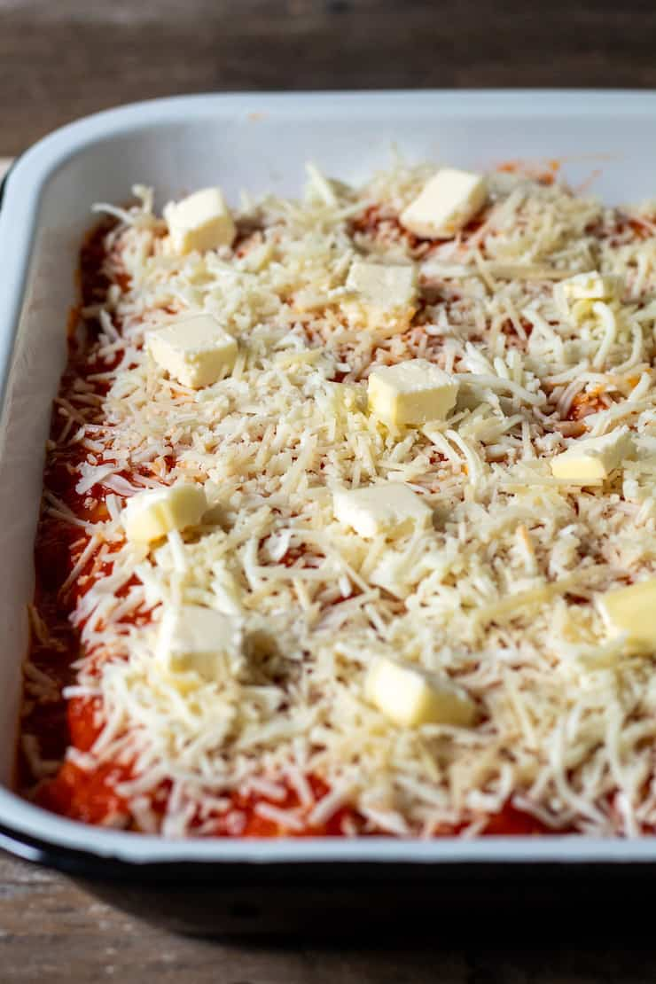 Assembled stuffed pasta tubes topped with shredded cheese and dotted with butter.