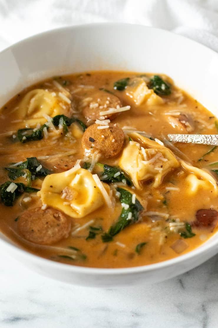 Bowl of Cajun tortellini soup with sppon.