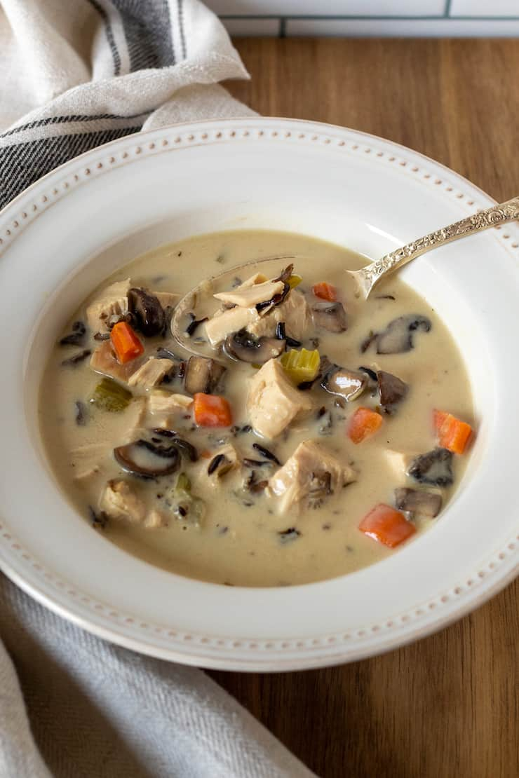 Overhead of bowl of chicken wild rice soup with spoon.
