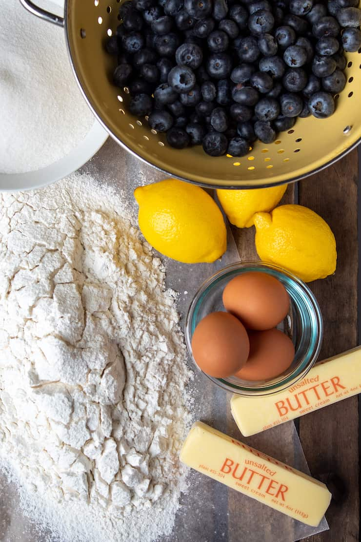 Ingredients photo, sifted flour, sugar, blueberries, lemons, eggs and butter.