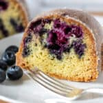 Close up of slice of cake on plate with fork and blueberries.