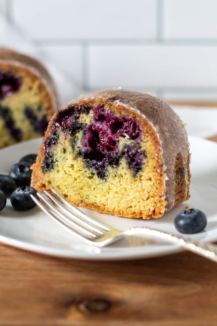 Slice of blueberry lemon Bundt cake on serving plate.
