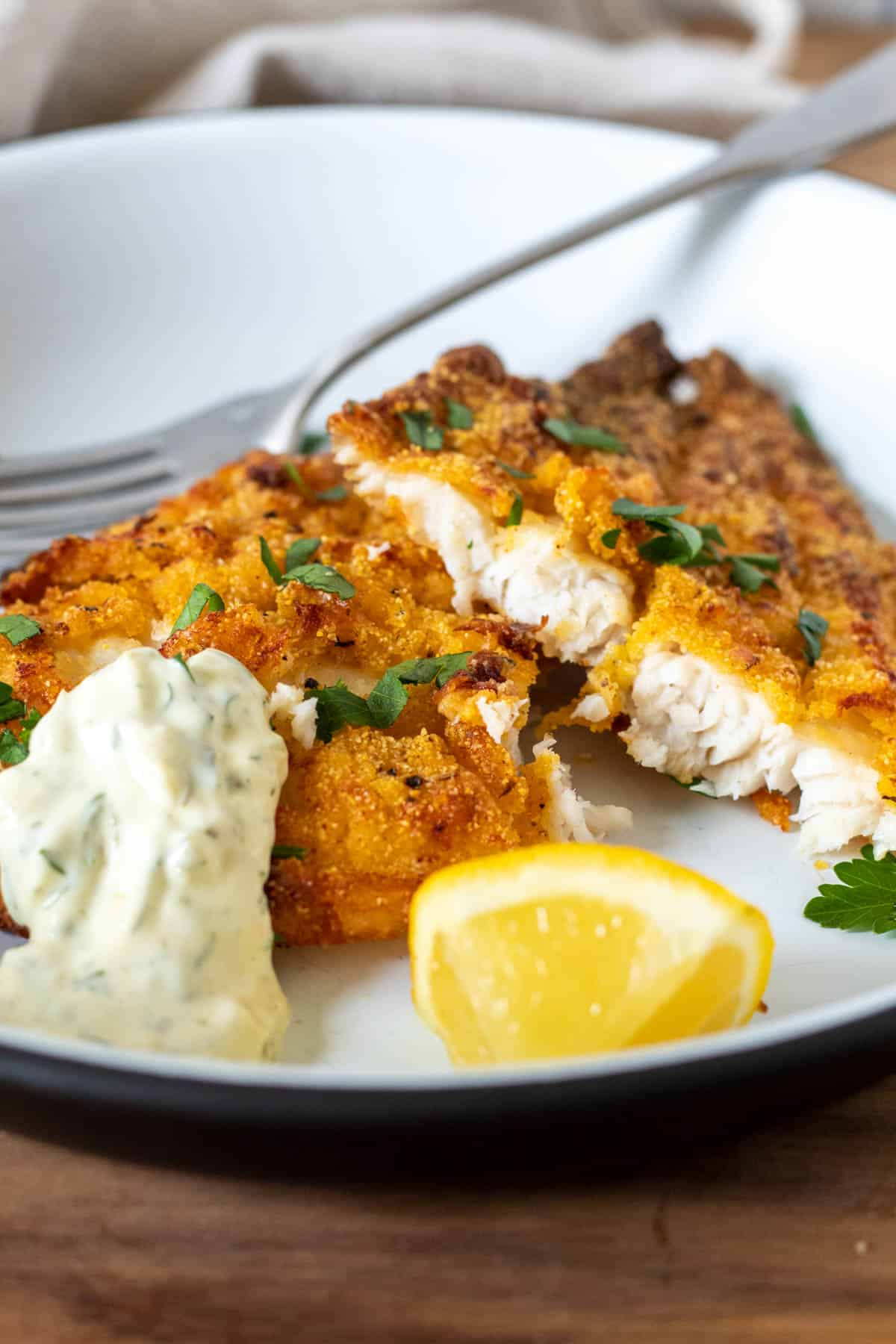 Air fryer southern catfish on plate with tartar sauce and lemon.
