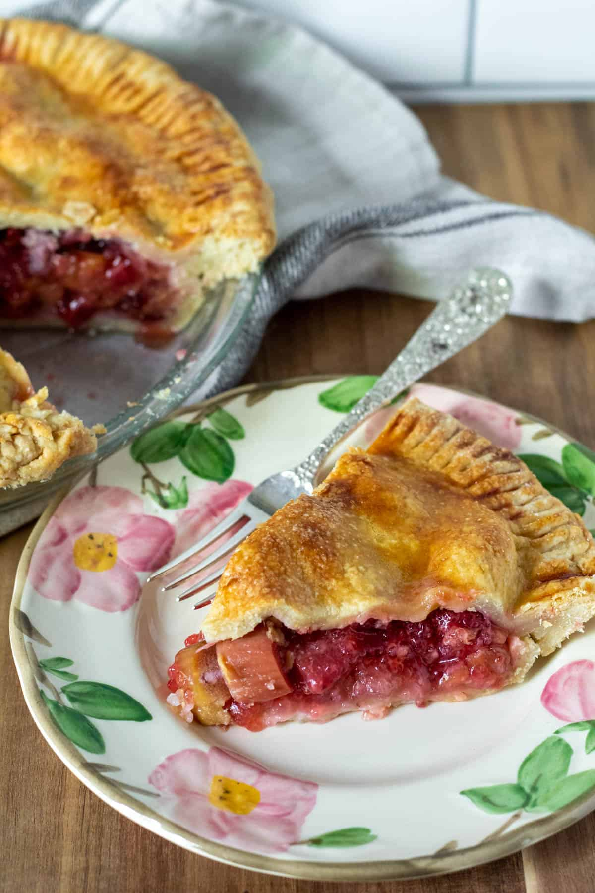 Pie on serving plate with whole strawberry rhubarb pie in background.