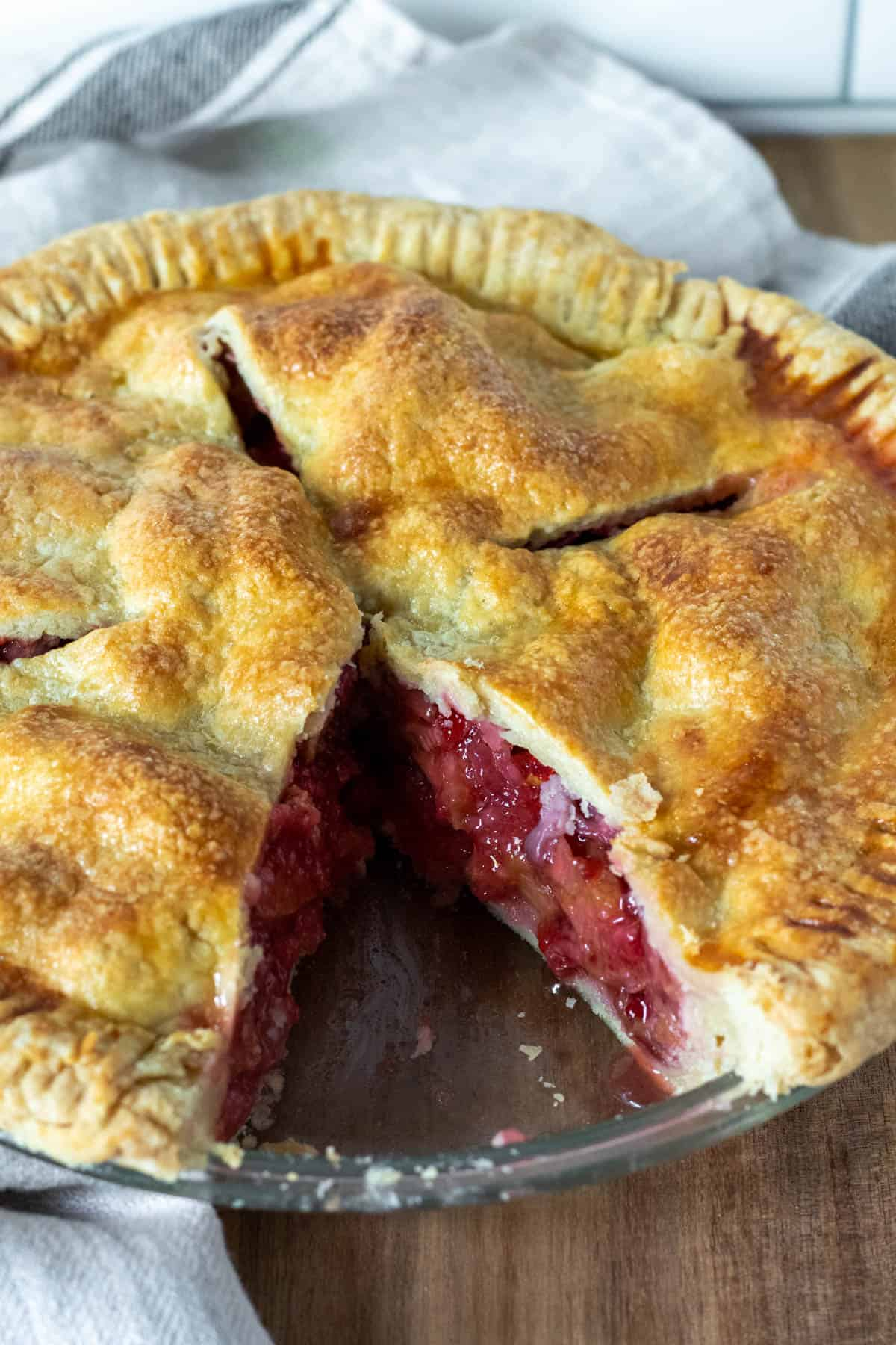 Close up of strawberry rhubarb pie with one piece cut out showing filling in crust.