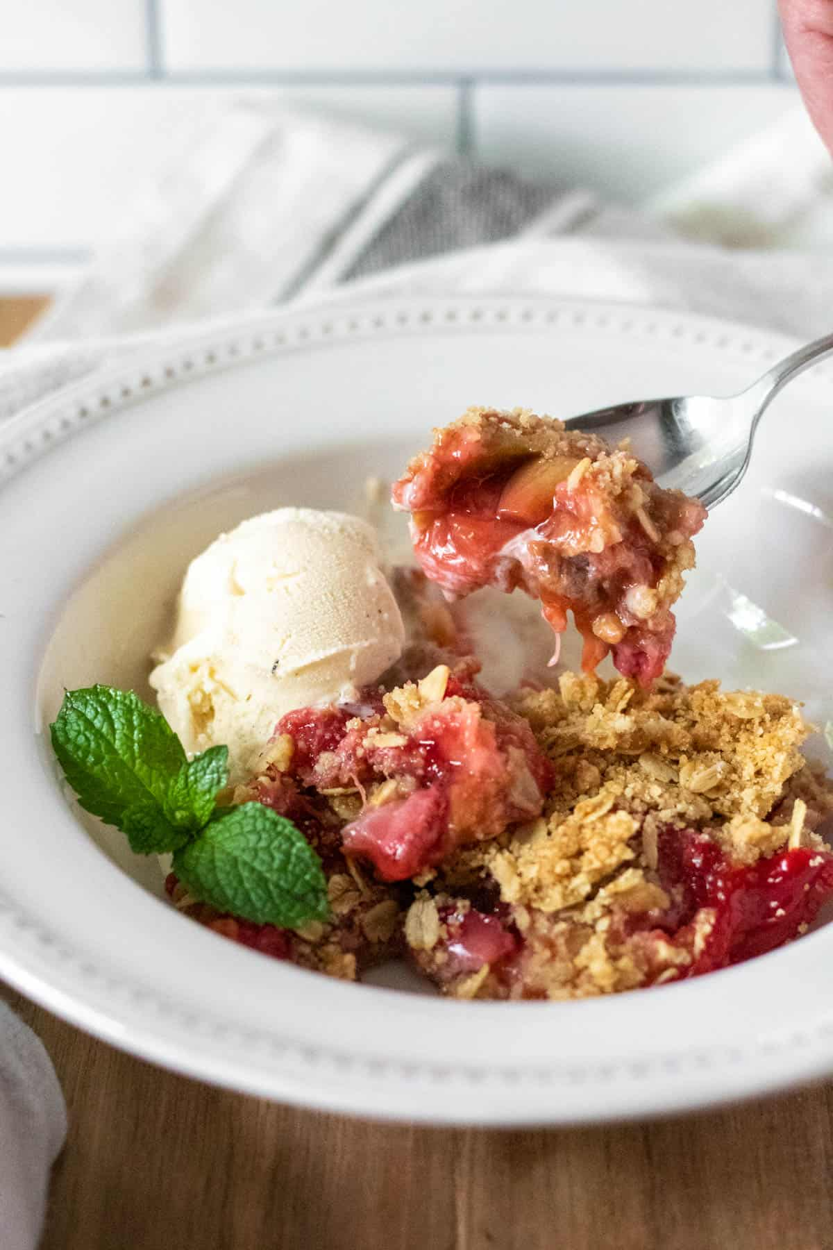 Spoonful of strawberry rhubarb crisp coming out of bowl with scoop of ice cream.