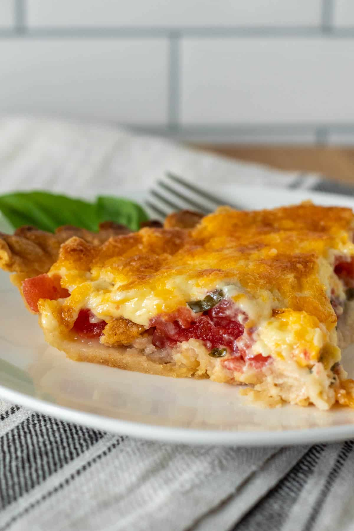 Piece of tomato pie on plate with fork.