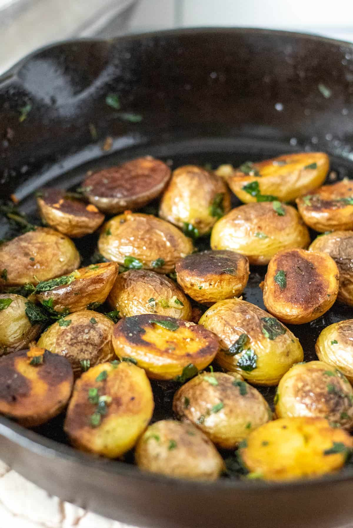 Potatoes cooked until brown and crispy in cast iron skillet.